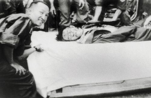 Một sĩ quan thuộc phe đảo chánh, vẻ mặt hớn hở, bên xác ông Nhu (không phải là ông Diệm như trong chú thích tiếng Anh)