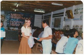 Cô Giáo Jenny đang nhận quà Giáng Sinh do đại diện trạitỵ nạn traotặng, năm 1982.