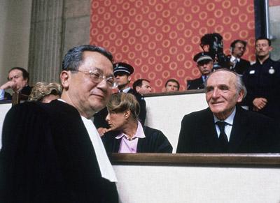 Klaus Barbie (phải), cựu trưởng mật vụ Gestapo thành phố Lyon, mỉm cười trong khi luật sư biện hộ Jacques Verges bước ngang qua trong phiên sơ thẩm xử ông Barbie vào ngày 11 Tháng Năm 1987.  (Hình: AP)