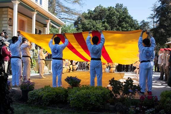 Các em võ sinh đang nâng đại kỳ VNCH trong nghi thức chào cờ.